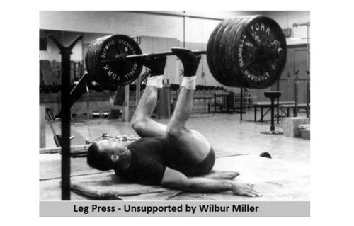 """a person lying on their back with their legs in the air, balancing a barbell with a total of 8 45 lb plates on it  the picture is captioned - """"Leg Press - Unsupported by Wilbur Miller"""""""
